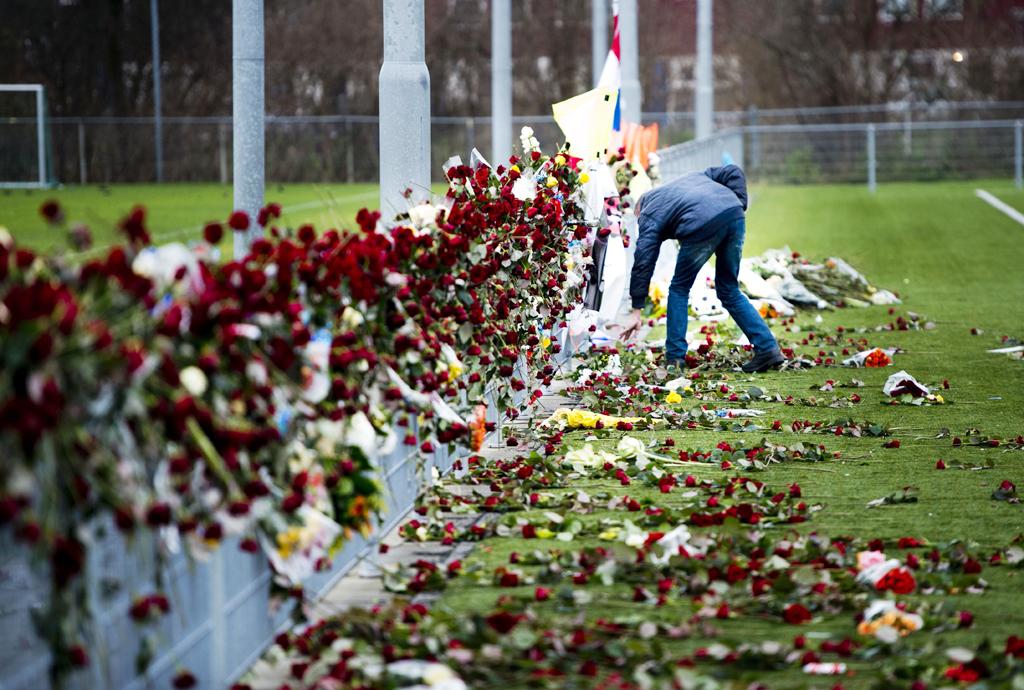 Een man rangschikt op de dag van de uitvaart van de overleden grensrechter Richard Nieuwenhuizen de bloemen bij het hek langs het veld van voetbalclub SC Buitenboys. Die werden daar een dag eerder neergelegd na afloop van de stille tocht voor Nieuwenhuizen.