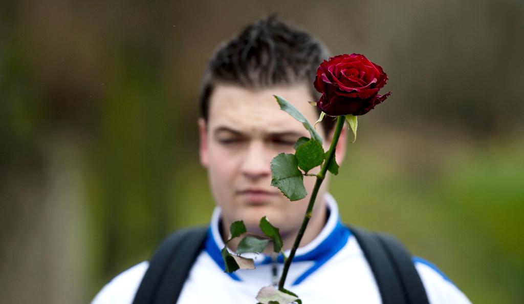 Een clublid van SC Buitenboys staat met een rode roos klaar voor de erehaag, voor aanvang van de uitvaart van de overleden grensrechter Richard Nieuwenhuizen.
