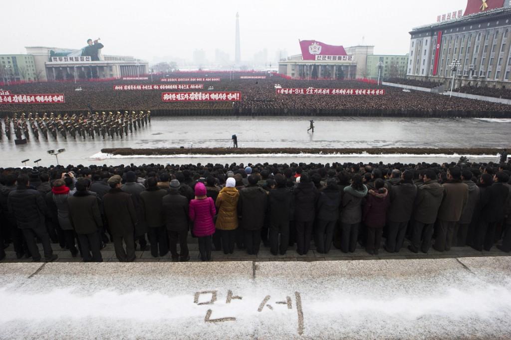 """In de sneeuw op een balkon bij het plein staat in het Koreaans """"Hoera"""" te lezen."""