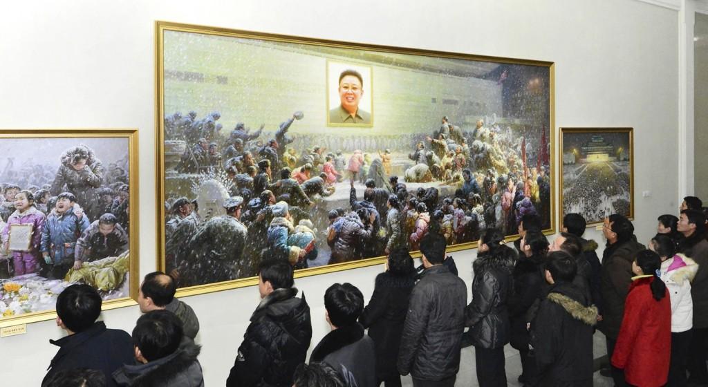 """Noord-Koreanen aanschouwen een schilderij ter nagedachtenis aan de overleden leider Kim Jong-il op de expositie """"De grote leider kameraad Kim Jong-il is voor altijd met ons"""". Aanstaande maandag is Kim Jong-il een jaar overleden."""