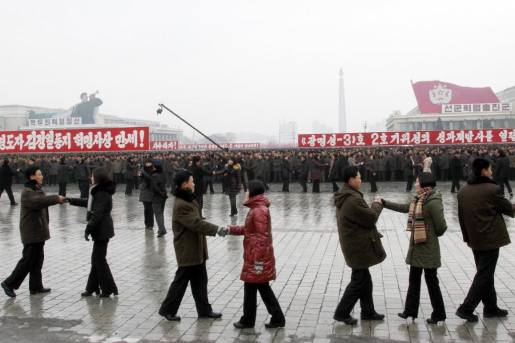 """Gedanst werd er ook, onder slogans als """"Hoera voor de revolutionaire ideologie van de grote leider kameraad Kim Jong II"""" en """"Wij vieren vurig de succesvolle lancering van de tweede versie van de Kwangmyongsong-3 satteliet"""" (de langeafstandsraket)"""
