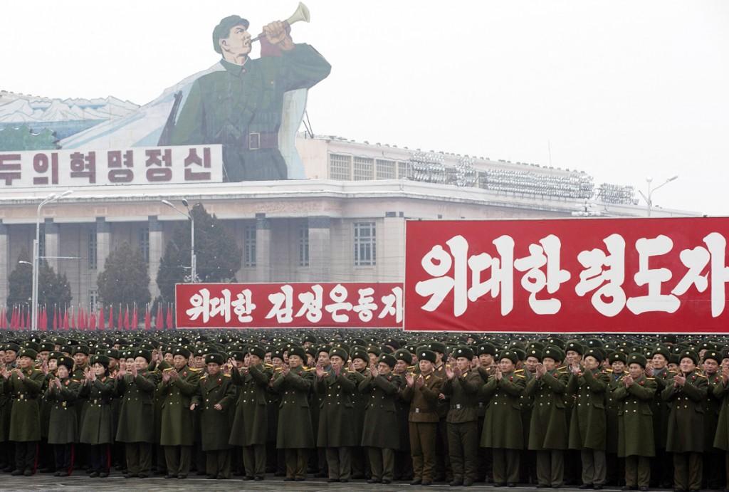 """Noord-Koreaanse soldaten applaudiseren op het plein in Pyongyang onder borden waarop """"Revolutionaire geest"""", """"Grote leider kameraad Kim Jong-un"""" en """"Grote leider"""" staat geschreven."""