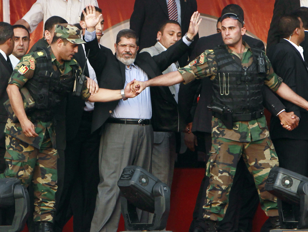 RNPS IMAGES OF THE YEAR 2012 - Egypt's Islamist President-elect Mohamed Mursi waves to his supporters while surrounded by his members of the presidential guard in Cairo's Tahrir Square, June 29, 2012. Mursi took an informal oath of office on Friday before tens of thousands of supporters in Cairo's Tahrir Square, in a slap at the generals trying to limit his power. REUTERS/Amr Abdallah Dalsh (EGYPT - Tags: POLITICS CIVIL UNREST TPX IMAGES OF THE DAY)