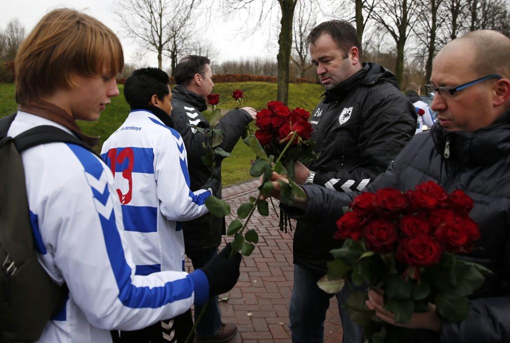Clubleden van SC Buitenboys ontvangen een rode roos voor de erehaag, voor aanvang van de uitvaart.
