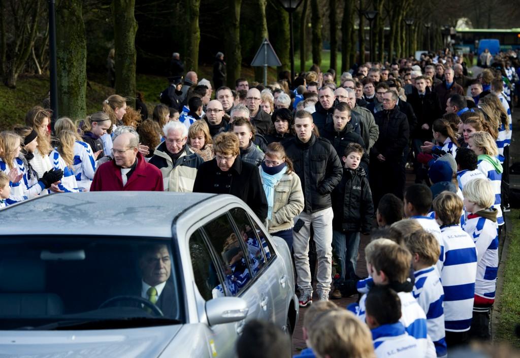 Een lange optocht van belangstellenden sluit de rouwstoet bij het crematorium.