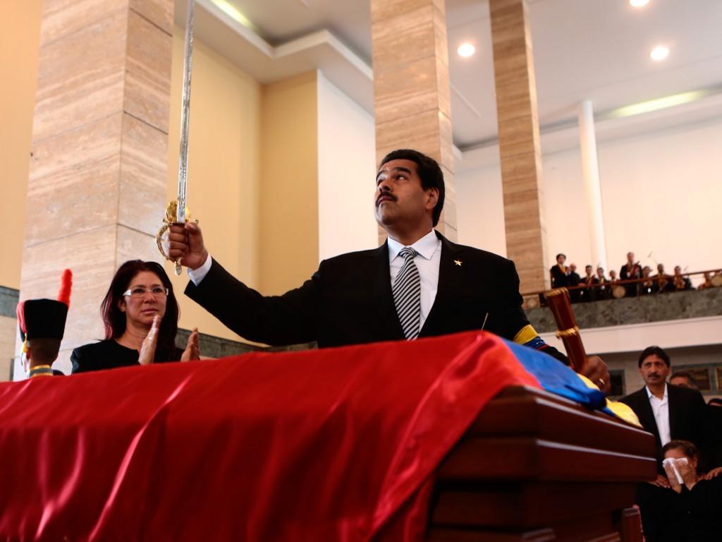 De Venezolaanse vicepresident houdt een replica van het gouden zwaard van Zuid-Amerikaans vrijheidsstrijder Simon Bolivar vast bij de kist van Chávez, tijdens de uitvaartceremonie. Erna wordt Maduro beëdigd als interim-president.