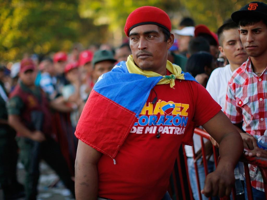 Een aanhanger van de overleden president met een Venezolaanse vlag in de rij om afscheid van Chávez te nemen.