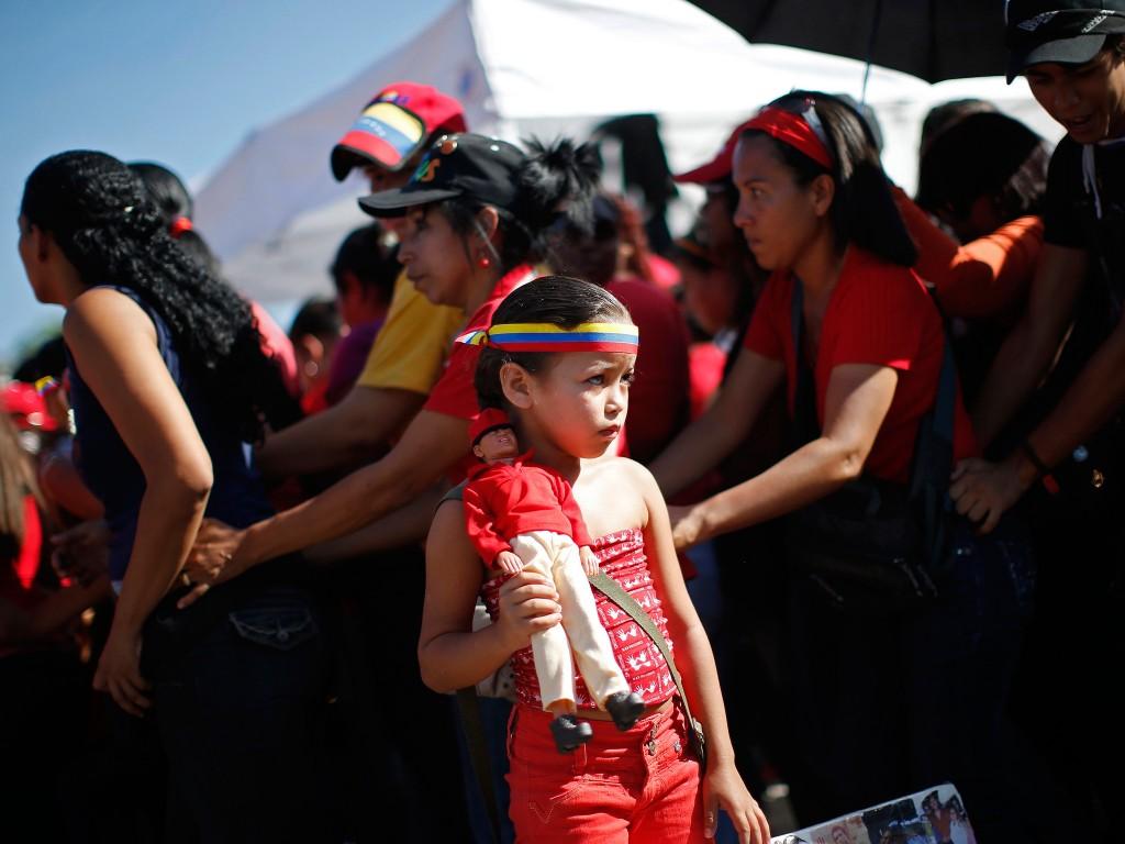 Een meisje houdt een pop vast van de overleden president Hugo Chávez, terwijl ze tussen andere aanhangers wacht tot ze van het opgebaarde lichaam van Chávez afscheid kan nemen.