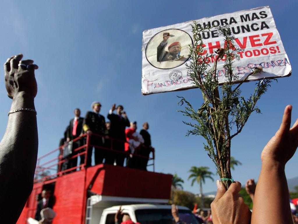 """Een aanhanger van Chávez houdt een bord vast terwijl interim-president Nicolas Maduro duizenden aanhangers toespreekt die wachten tot ze afscheid kunnen nemen van Chávez. Op het bord staat """"Nu meer dan ooit, zijn wij allen Chávez."""" Volgens de Venezolaanse overheid bezochten al meer dan twee miljoen aanhangers de militaire academie waar Chávez op ligt gebaard."""