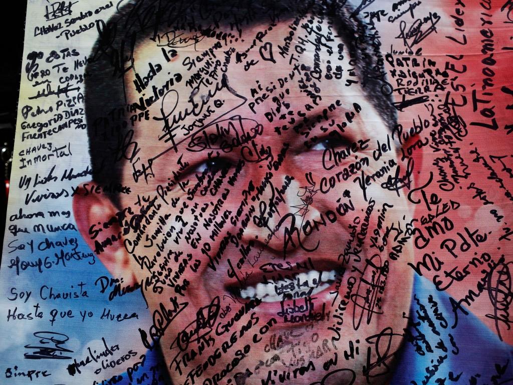 """Een poster van Chávez voor de militaire academie in Caracas, waar hij ligt opgebaard, staat volgeschreven met berichten van zijn aanhangers, zoals """"Mijn eeuwige president"""" en """"Ik ben een Chávist totdat ik sterf""""."""