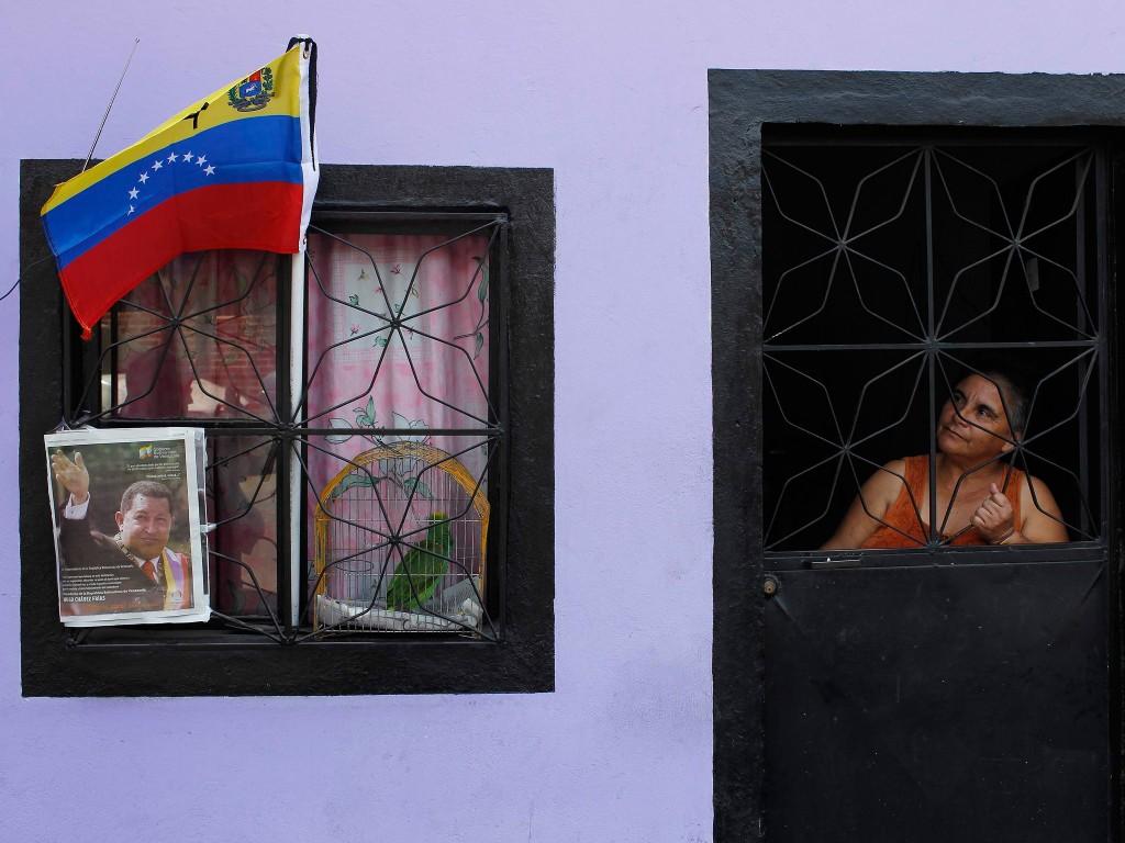 Een vrouw kijkt in Caracas, de hoofdstad van Venezuela, uit haar raam naar een vlag en het portret van Chávez. Venezolaanse burgers nemen deze dagen massaal afscheid van hun overleden president.