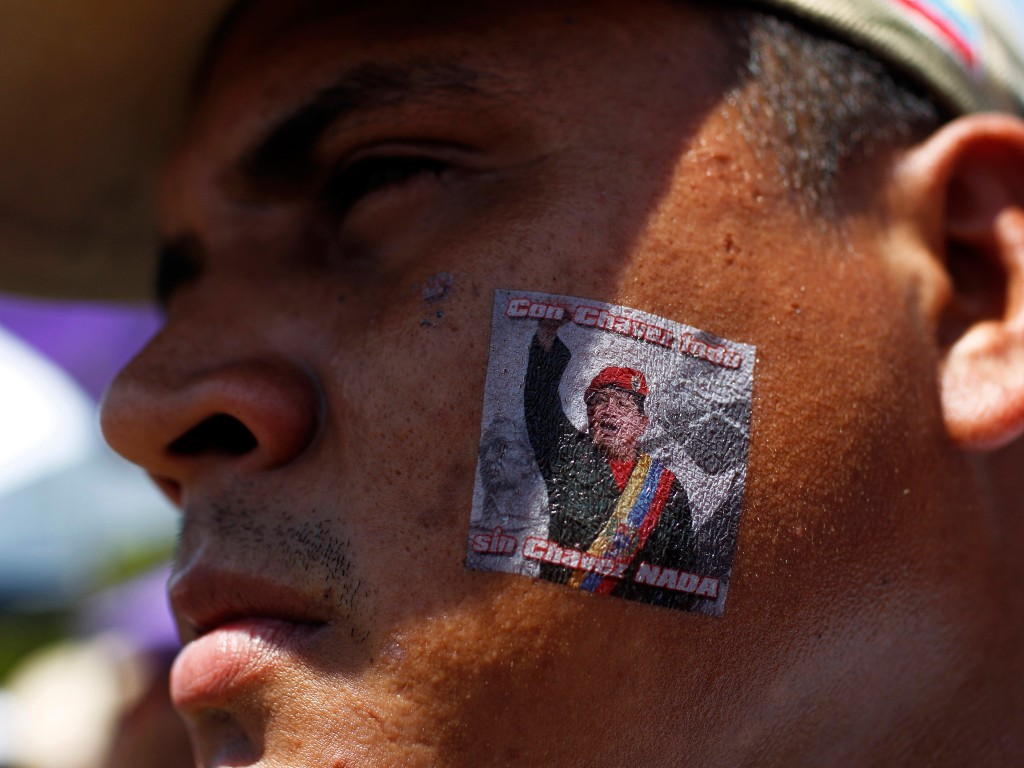 Een Chávez-sticker op de wang van een rouwende aanhanger.