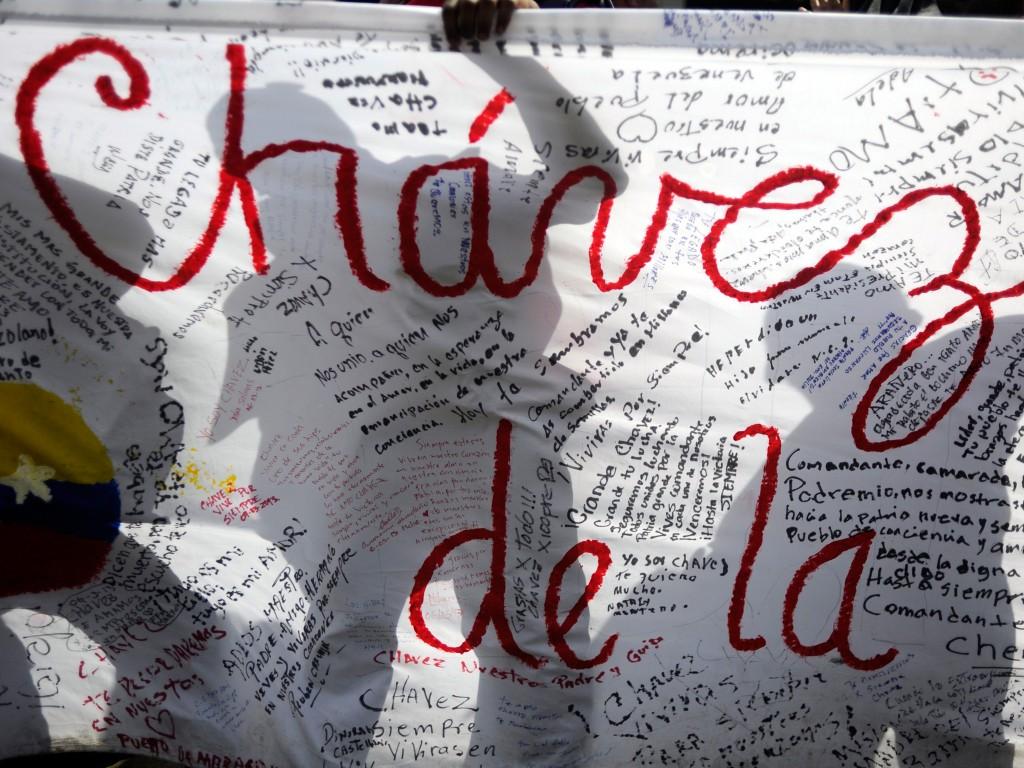 Aanhangers hebben teksten voor Chávez bij zich in de rijen bij de militaire academie.