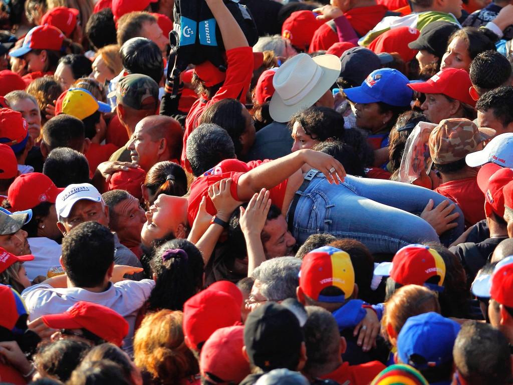 Een aanhanger van Chávez wordt uit de menigte getild nadat ze is flauwgevallen in de rij voor de militaire academie in Caracas waar Chávez ligt.