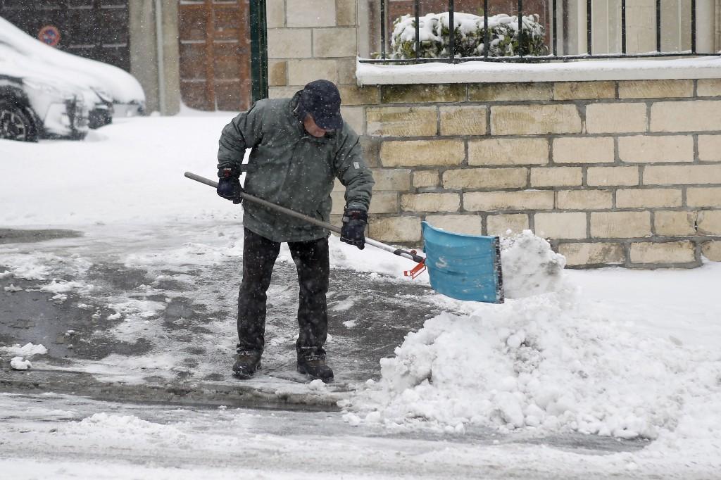 Een man in Caen laat zich niet afschrikken door de centimeters sneeuw.