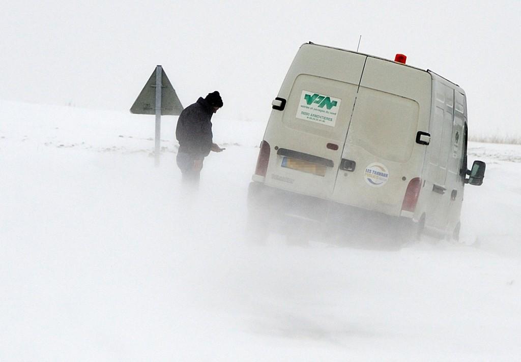 Een automobilist belt hulp voor zijn vastgereden busje in Godewaersvelde, Noord-Frankrijk.