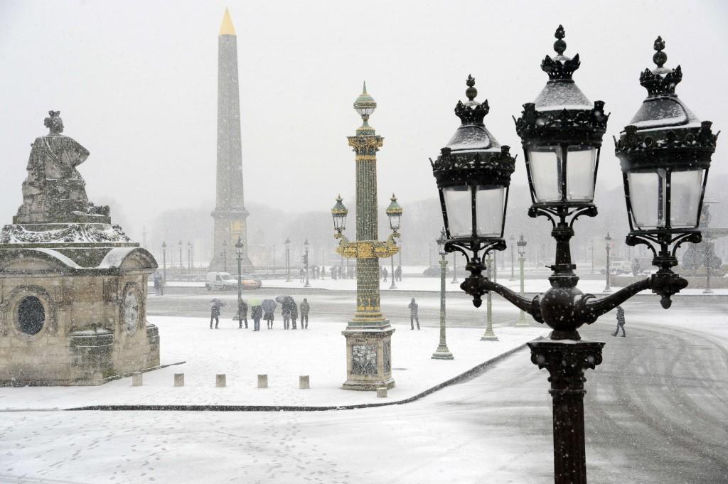 De ondergesneeuwde Place de la Concorde in Parijs. Meer dan 68.000 huishoudens kwamen in Frankrijk zonder electrictiteit te zitten, honderden konden niet meer verder met de auto.