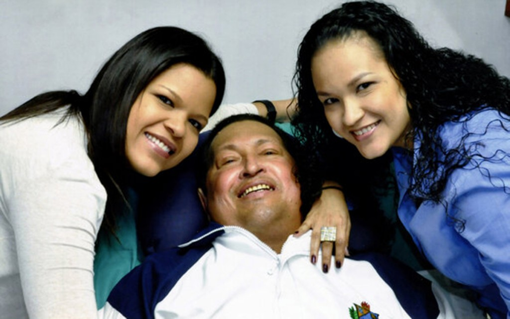 File photo of Venezuela's President Hugo Chavez smiling in between his daughters while recovering from cancer surgery in Havana