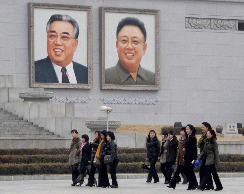 Noord-Koreaanse vrouwen lopen langs de portretten van Noord-Korea's stichter Kim Il-sung en de vorige leider, Kim Jong-il.
