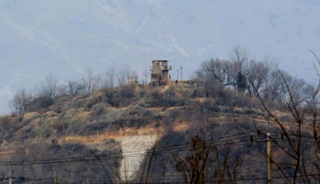Noord-Koreanen lopen bij de wachttoren langs de grens.