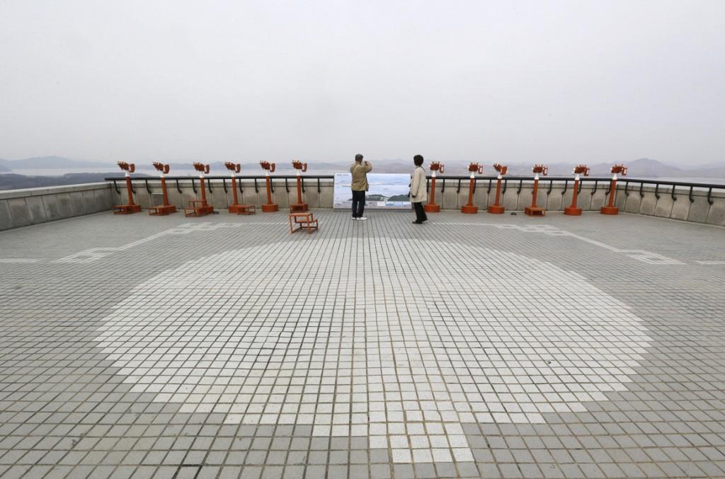 Bezoekers nemen foto's van het Noord-Koreaanse territorium bij de observatiepost aan de grens.