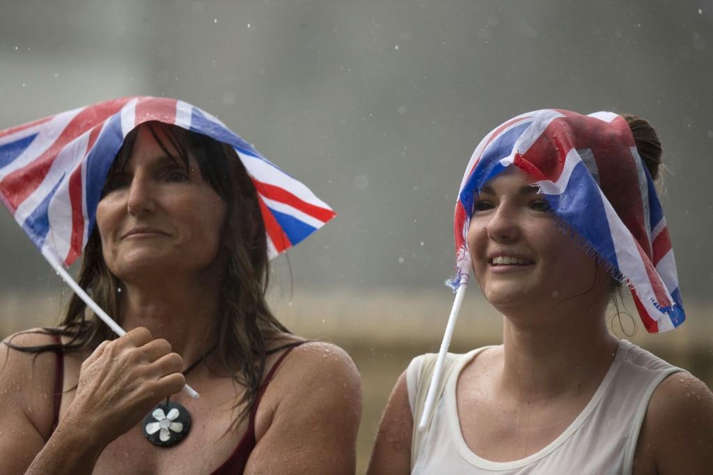 Twee vrouwen, doorweekt van de regen, staan buiten het ziekenhuis in afwachting van het prinsje