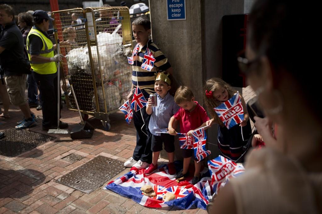 Kinderen, onder toezicht van hun familieleden, poseren voor een foto buiten St. Mary's Hospital in Londen in afwachting van het moment dat de prins getoond wordt aan het publiek.