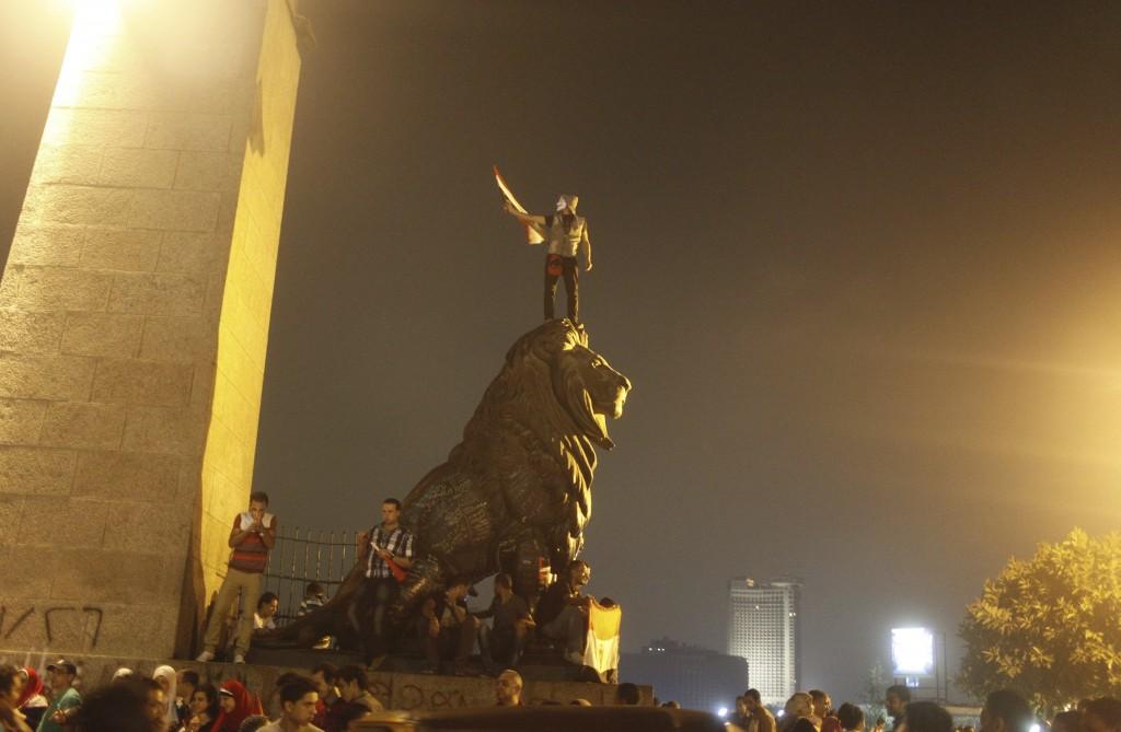 Een demonstrant staat op een standbeeld op het Tahrirplein met een Guy Fawkes-masker.