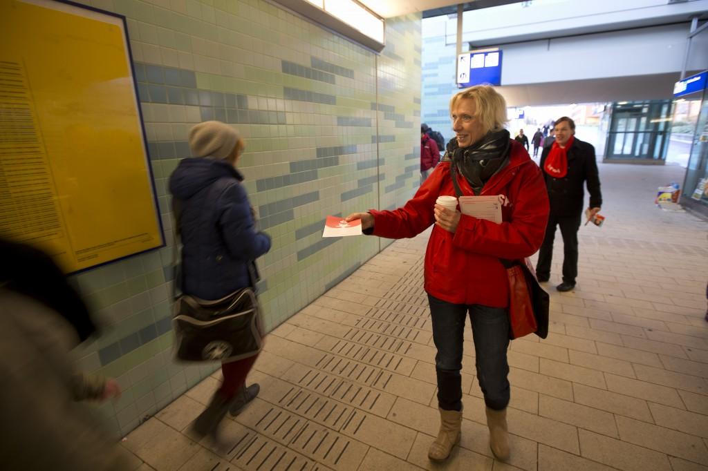 Mensen flyeren voor de SP op het station van Alphen aan de Rijn