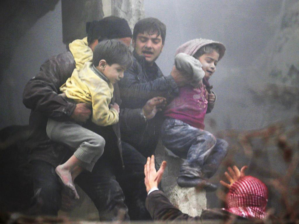 Mannen helpen kinderen die een luchtaanval, volgens activisten gepleegd door troepen van president Assad, hebben overleefd.