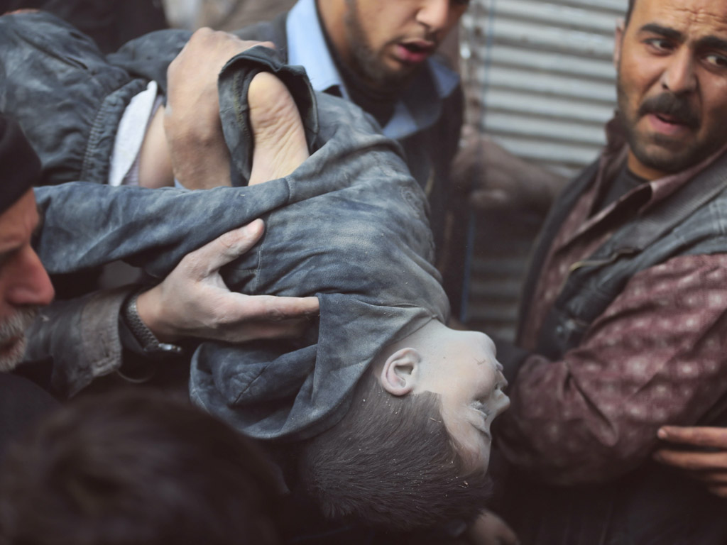 Mannen dragen het lichaam van een jongetje dat onder het puin vandaan is gehaald.