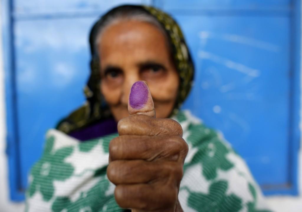 Een vrouw toont haar vinger waar onuitwisbare inkt op zit. Ze heeft zojuist gestemd.