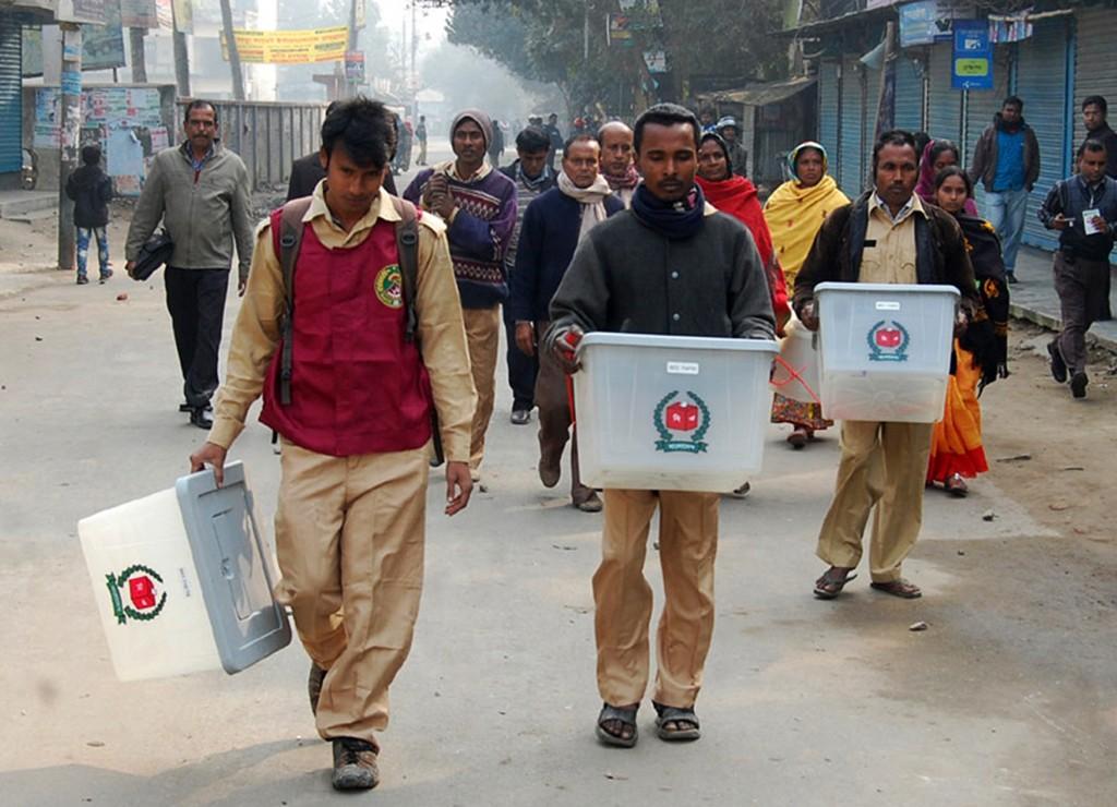 Verkiezingsambtenaren dragen enkele stembussen die ze hebben kunnen redden na een aanval op een stemkantoor in Bogra.