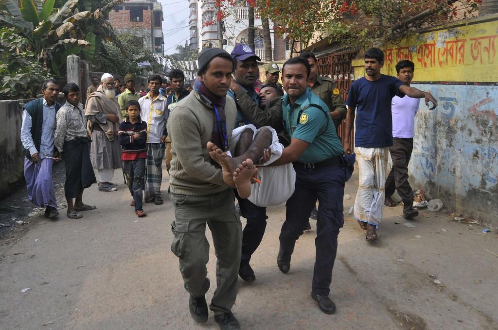 Politie en vrijwilligers in Dhaka dragen een stemmer die zojuist gewond is geraakt toen oppositieaanhangers een bom gooiden.