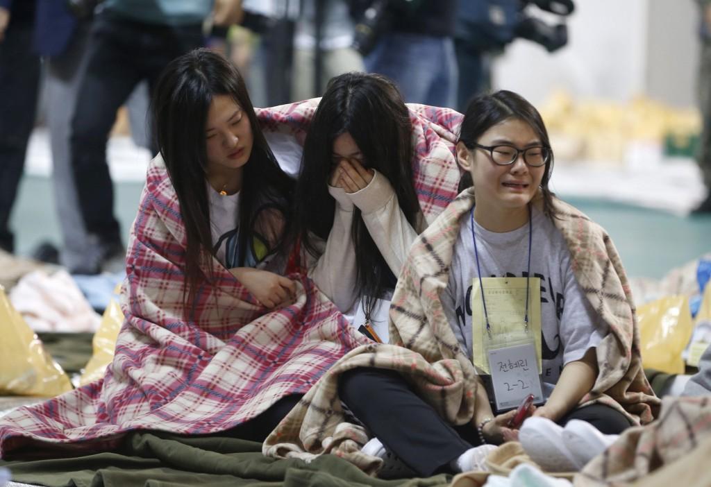 Passagiers, gered vanaf het schip, zitten verslagen in een gymzaal in Jindo.