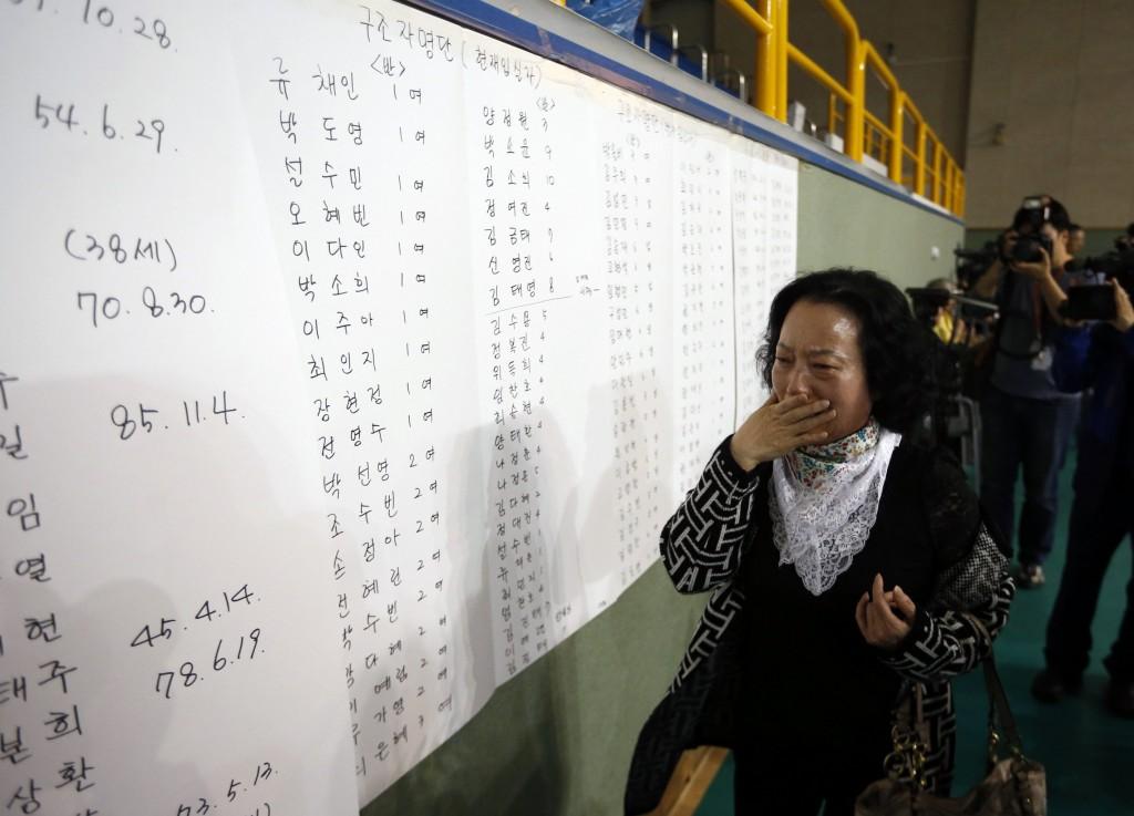 De moeder van een van de passagiers reageert emotioneel wanneer ze ziet dat de naam van haar zoon op een lijst met overlevenden staat.