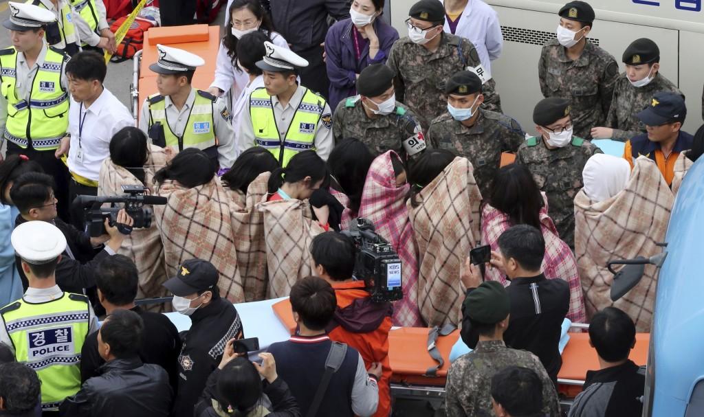 Passagiers worden door de reddingsdiensten begeleid bij hun aankomst in de haven van Jindo.