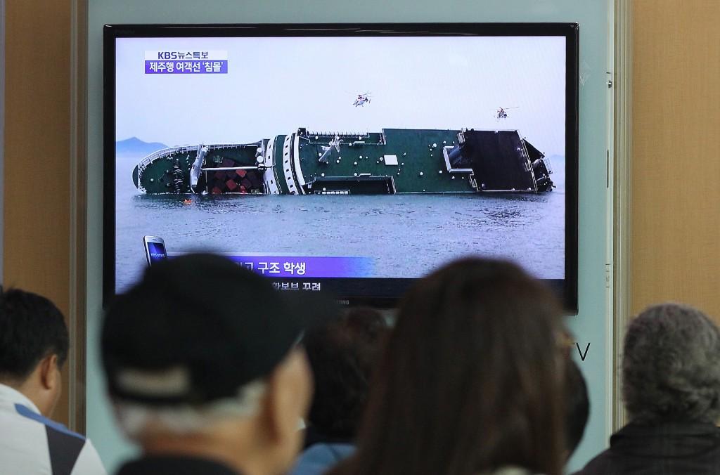 Op tv veel aandacht voor het ongeluk. Mensen kijken naar het zinkende schip op een station in hoofdstad Seoul.