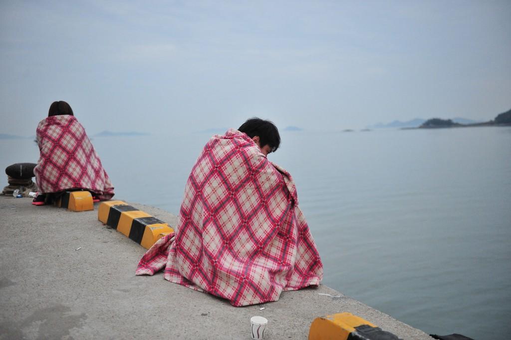 Familieleden van vermiste passagiers wachten in de haven van Jindo op nieuws.