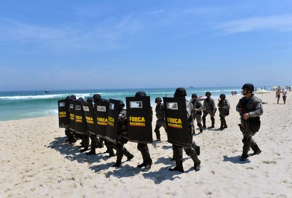 Het Braziliaanse Forca National oefent op demonstranten op het strand in Barra de Tijuca, Rio de Janeiro.