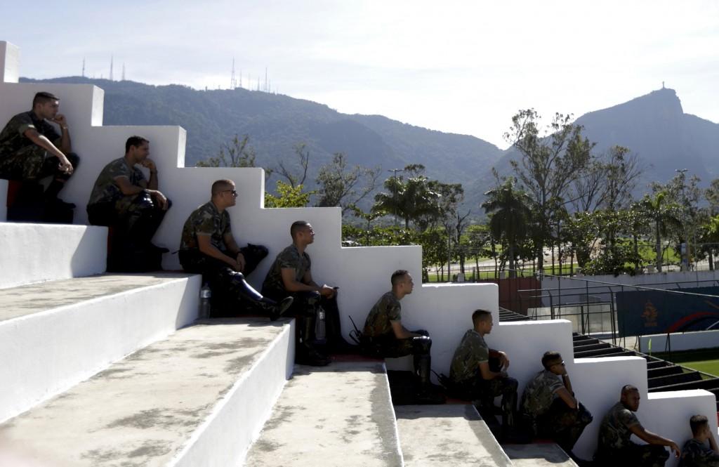 Braziliaanse soldaten zitten in de schaduw en kijken naar een training van het Nederlands voetbalelftal.