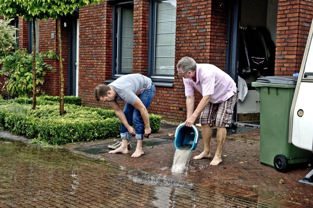 Inwoners van de Vaartstraat in Kaatsheuvel ruimen met emmers het water voor hun deur op. Een groot deel van het dorp stond blank. In Kaatsheuvel moest een verzorgingstehuis worden ontruimd vanwege de hevige regenval.