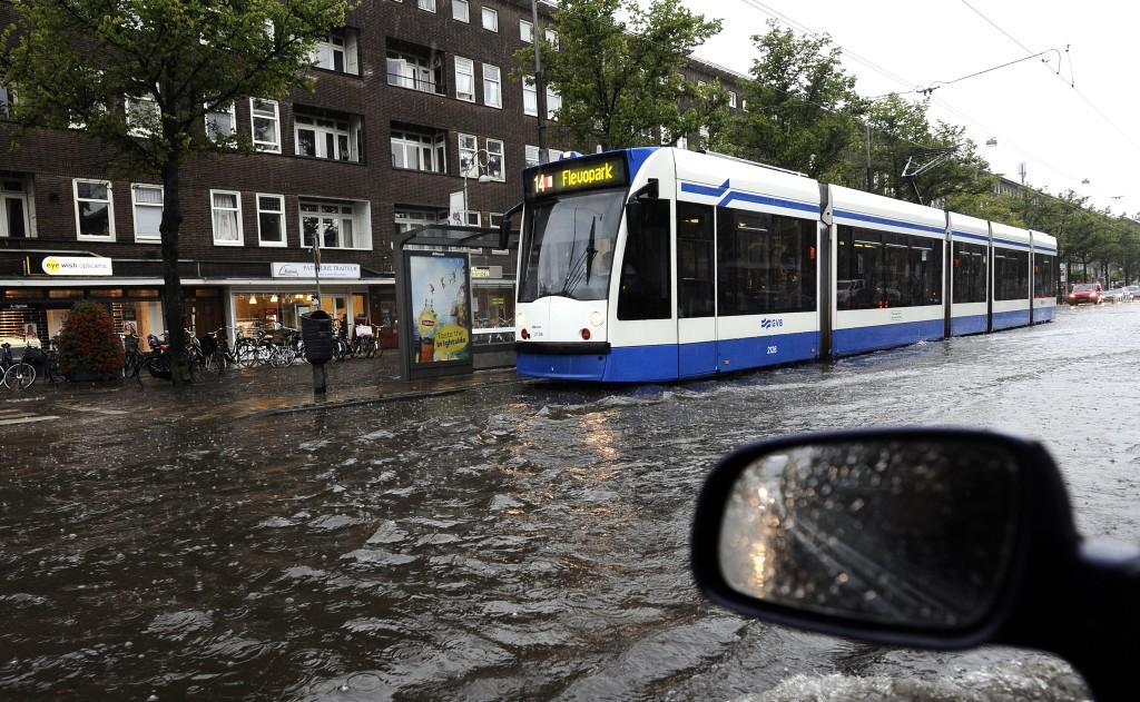 Tram 14 rijdt door de ondergelopen straat in Amsterdam.
