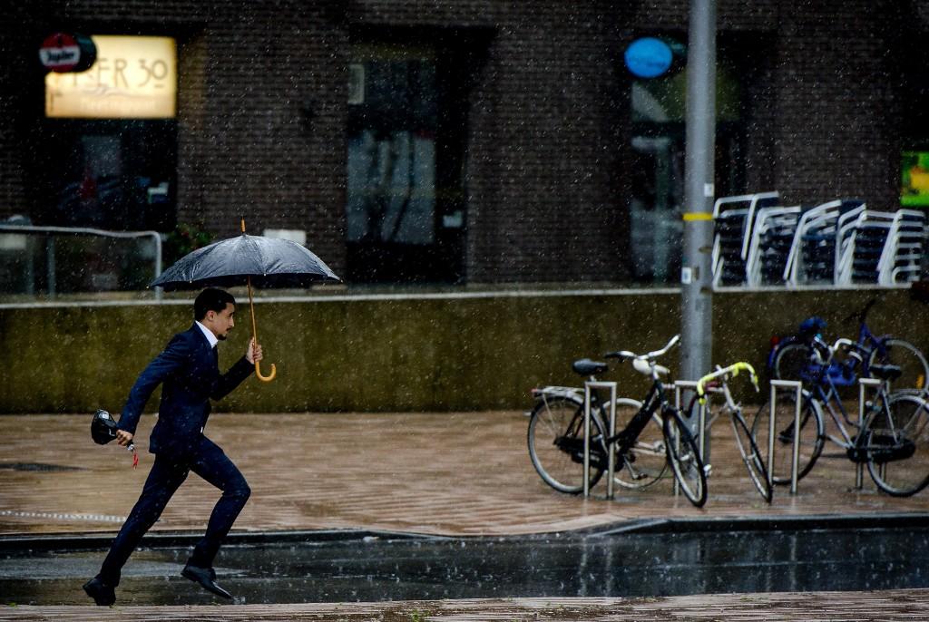 Een voetganger trotseert de regen in Rotterdam.