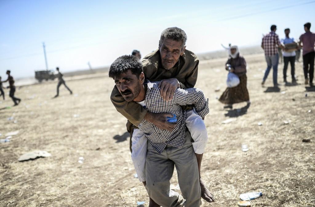 Een man draagt een oudere Koerdische man op zijn rug