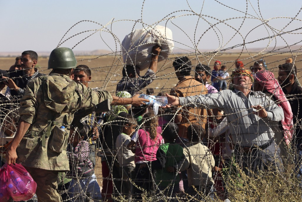 Een Turkse soldaat geeft een gehandicapte Syrische vluchteling die bij de grensovergang wacht water.