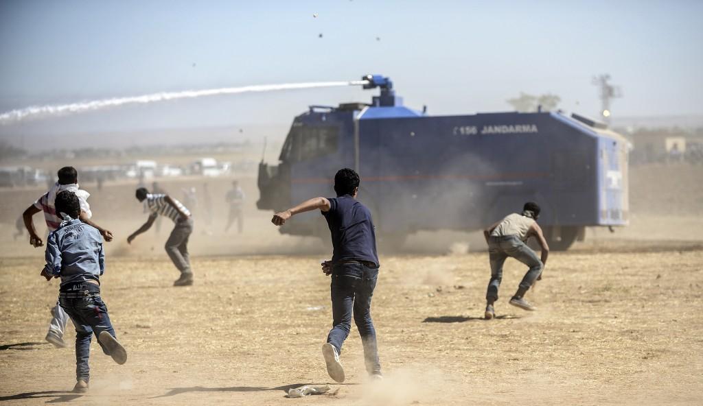 Koerdische demonstranten raken slaags met Turkse soldaten bij de Syrische grens. Turkije had kort daarvoor de grensovergang bij Suruc tijdelijk gesloten.