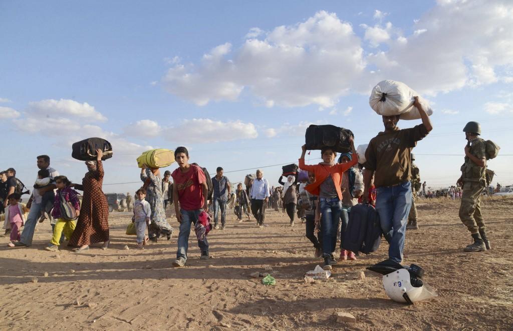 Syrische Koerden lopen met hun eigendommen de grens over.