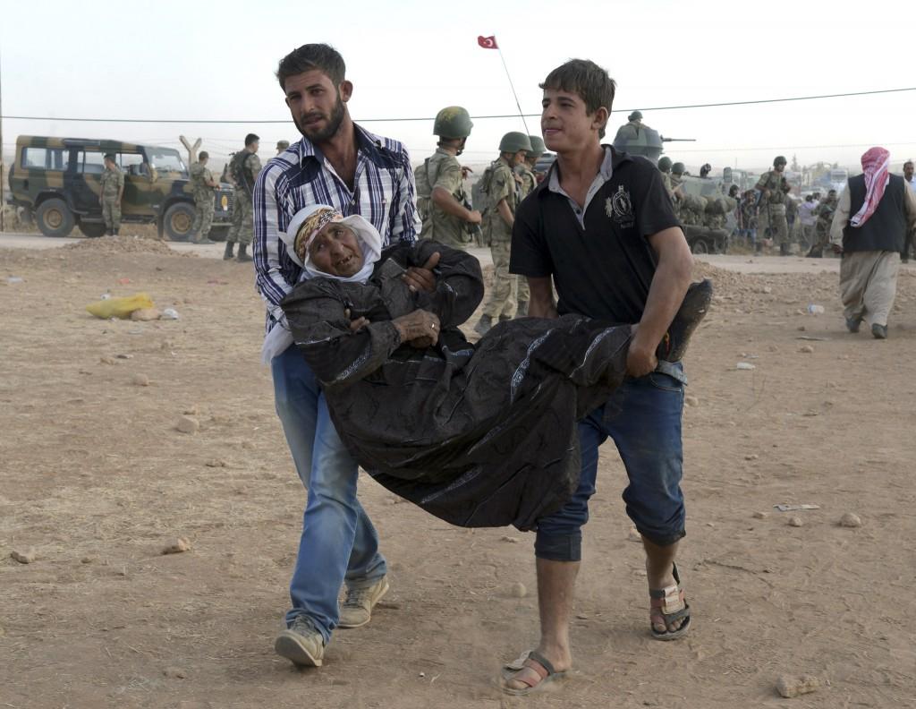 Jongere vluchtelingen dragen een zieke landgenoot de grens over.