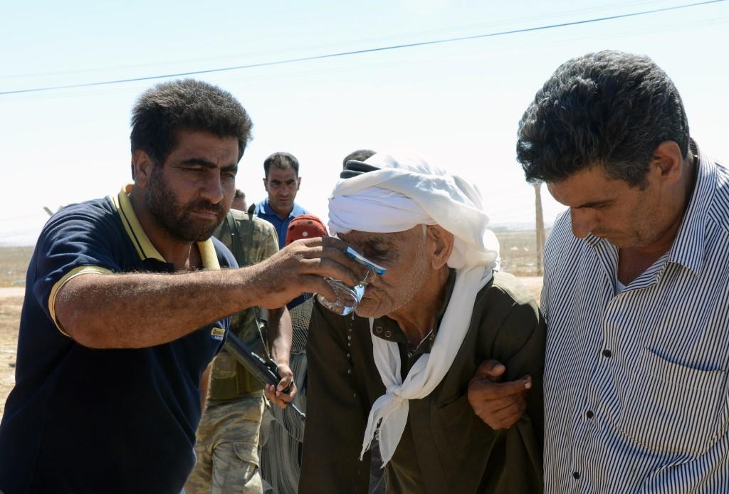 Mensen bieden een Syrische vluchteling water aan bij de grensovergang in Suruc, Turkije.